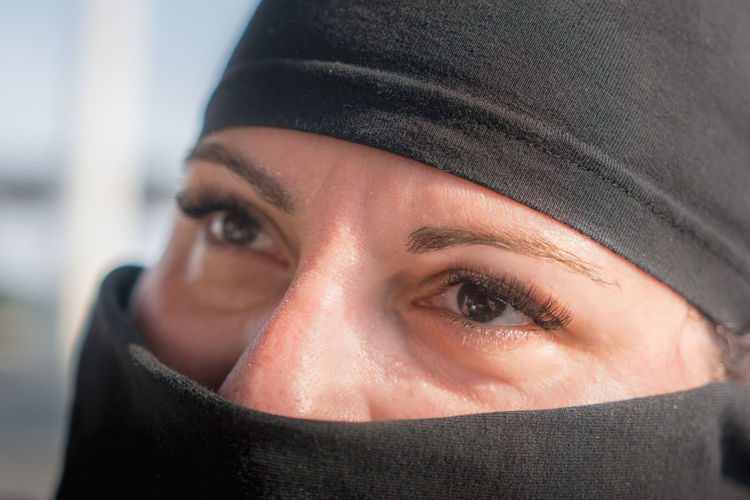Close-up portrait of mid adult woman covering face