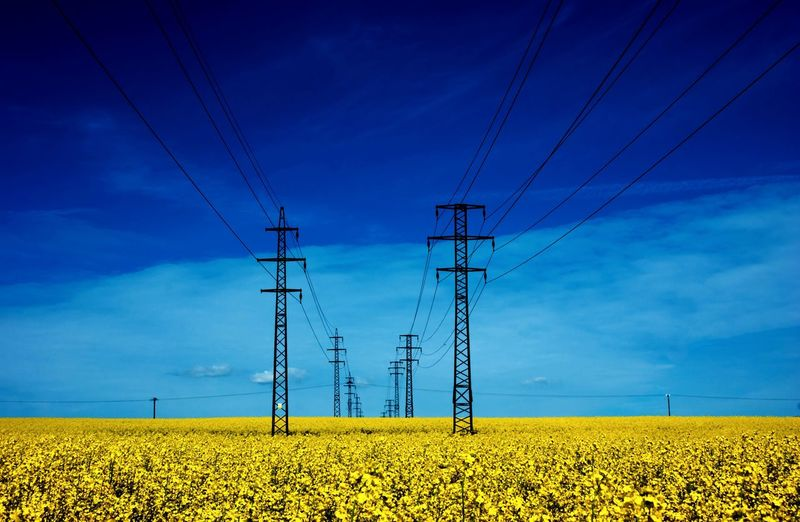 Electricity pylon on field against blue sky