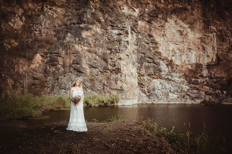 Portrait of woman wearing wedding dress holding bouquet standing by water against rock