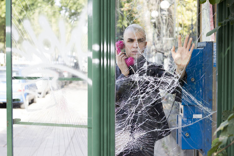 Portrait Of Bald Man Using Telephone Booth Seen Through Shattered Glass9