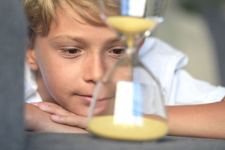 Handsome blond smiling guy lying with his hands under his face looks dreamily fascinated slow-moving sand in glass hourglass. rapt gaze, concept of desire that time runs desires are quickly realized One Person Portrait Child Headshot Holding Men Childhood Science Looking Close-up Indoors  Males  Scientific Experiment Boys Education Front View Pre-adolescent Child Glass