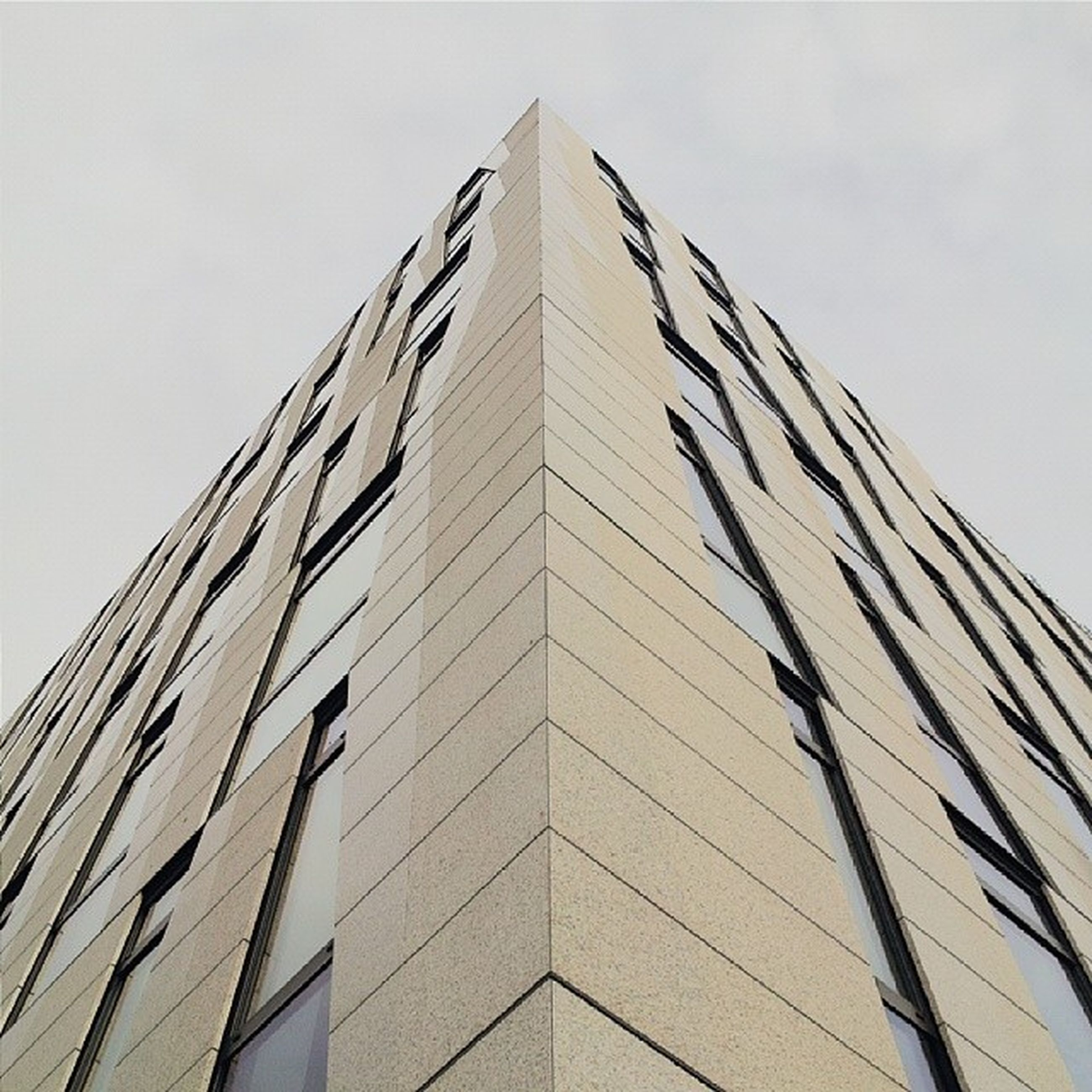 architecture, low angle view, building exterior, built structure, tall - high, modern, office building, city, tower, building, skyscraper, window, sky, clear sky, glass - material, tall, day, outdoors, no people, architectural feature