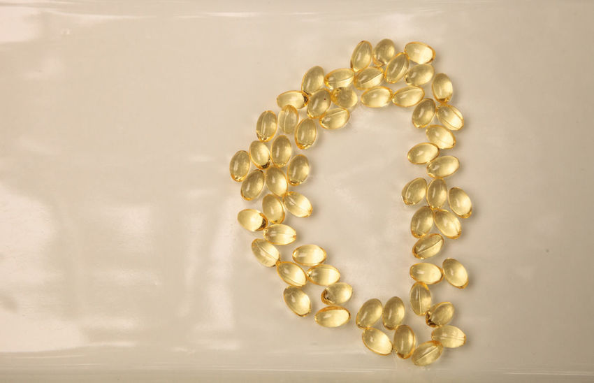 Liquid gold gel capsule of vitamin D displayed on a white surface. D Vitamin D Alternative Therapy Capsules Gel Caps Gel Capsules Gold Pills Healthy Liquid Pills Natural Therapy Nutrition Nutritional Supplement Vitamin Yellow Pills