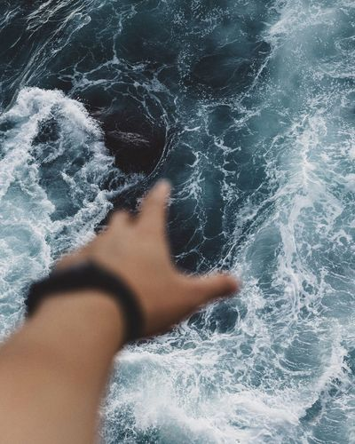 Cropped Image Of Person Hand Against Sea