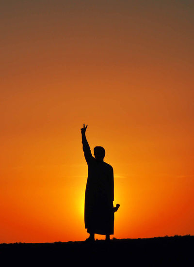 Sunset Silhouette One Person Orange Color Sky Leisure Activity Arms Raised Copy Space Human Arm Real People Men Standing Lifestyles Rear View Freedom Beauty In Nature Sitting Full Length Outdoors Sunrise Sun Scenics