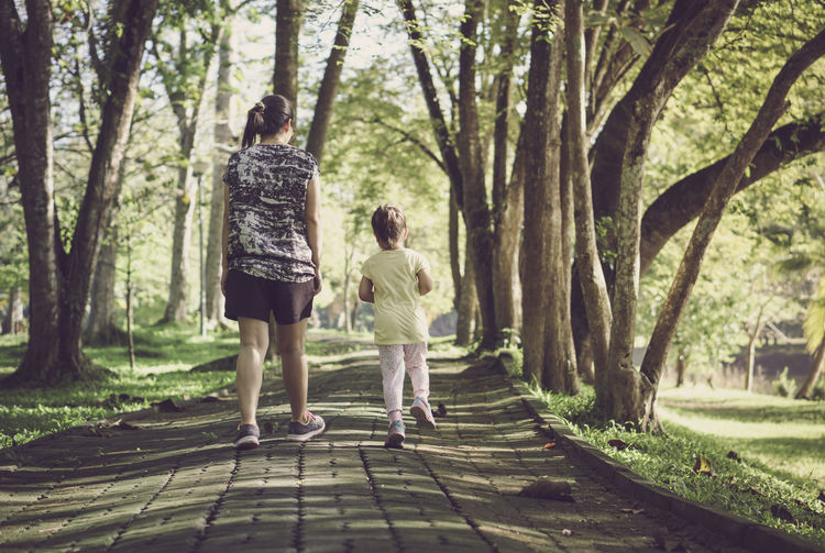 Rear view of mother and daughter walking on footpath at park