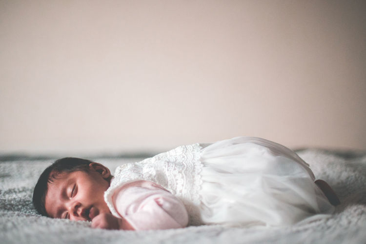 Cute Baby Girl Sleeping On Bed At Home