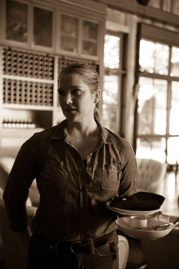 Young woman with plates and bowl standing in winery