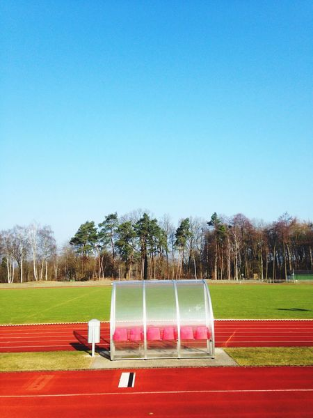 Sport No People Blue Clear Sky Sky Day Running field Outdoors waiting Red Color stadium yard line Track And Field Sport track Training