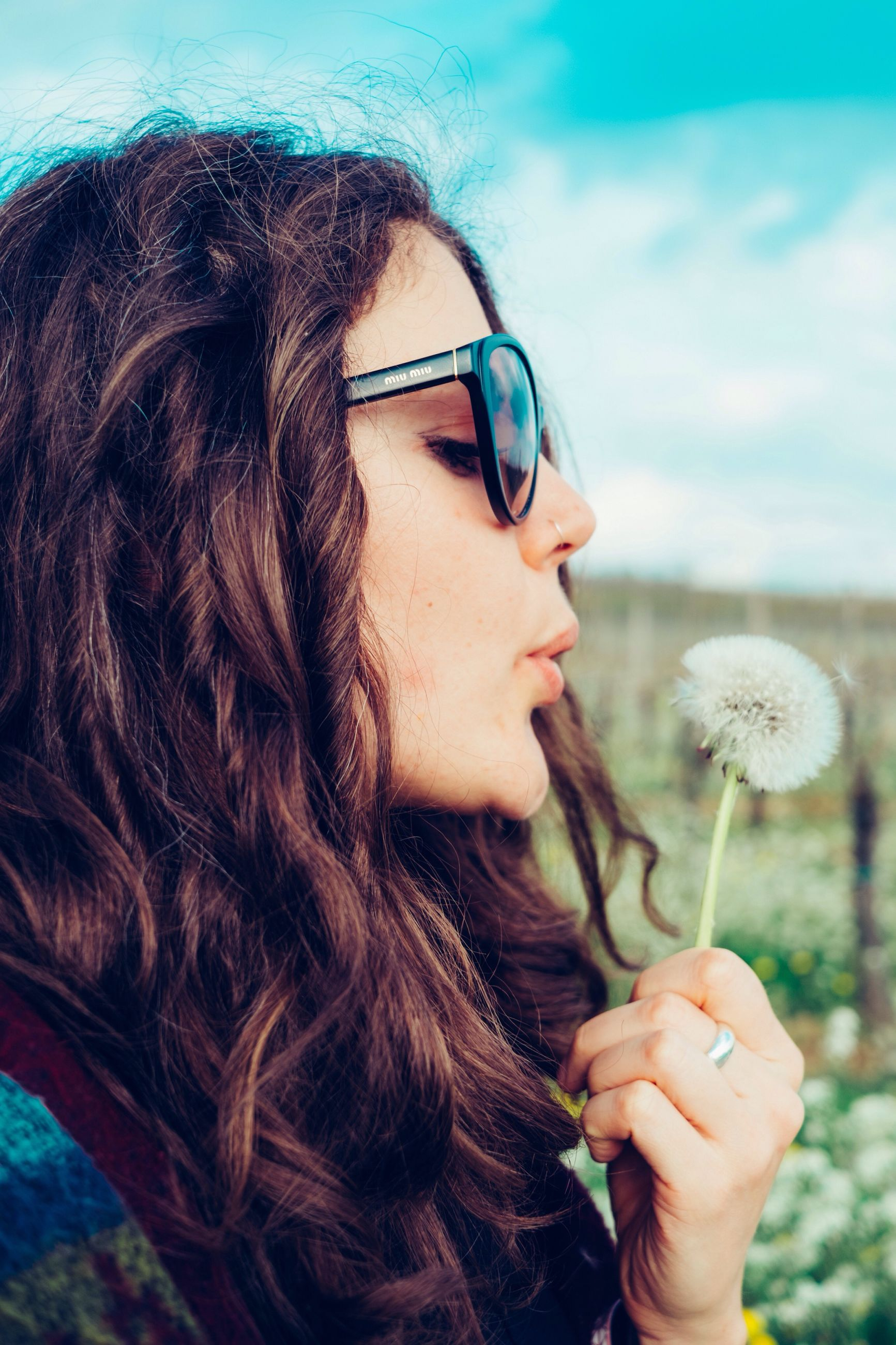 young adult, person, headshot, lifestyles, young women, long hair, leisure activity, focus on foreground, holding, front view, close-up, portrait, sunglasses, looking at camera, human face, head and shoulders