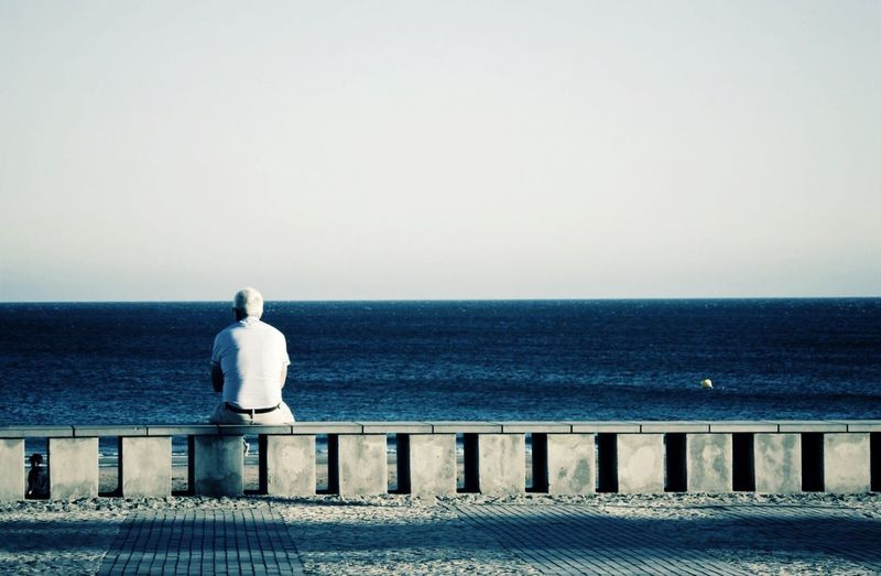 Rear view of man sitting on retaining wall by sea against clear sky