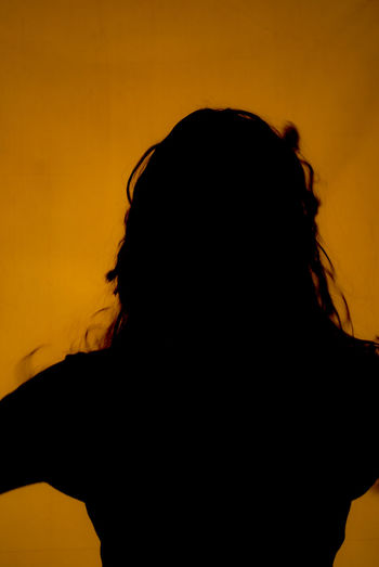 Rear view of silhouette woman against orange sky