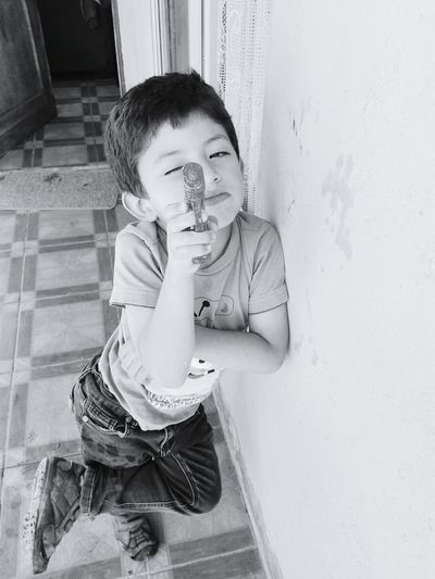Portrait of little boy aiming with toy gun