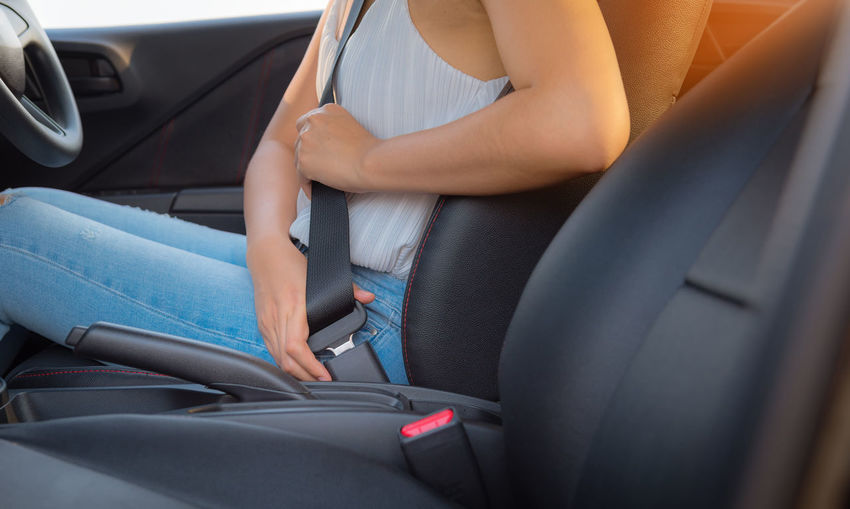 Midsection of woman wearing seat belt in car
