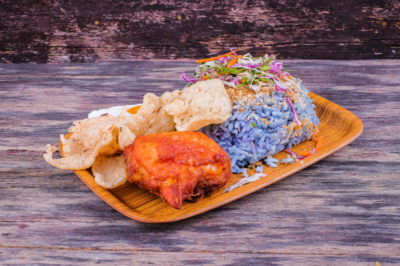 Nasi kerabu traditional in Malaysia food. Its blue color. Use coconut which has been fried and mixed with rice. A combination of vegetables, duck eggs and side dishes Close-up Day Food Food And Drink Freshness Fried Chicken Healthy Eating Meat No People Paper Plate Plate Ready-to-eat Wood - Material