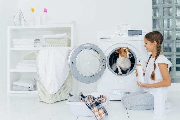 Smiling girl looking at dog in washing machine