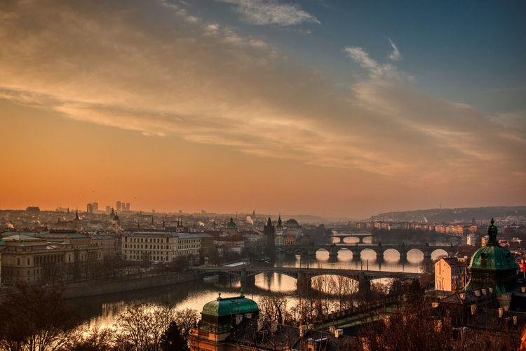 Prague bridges panorama during mist fog morning sunrise warm light red sky
