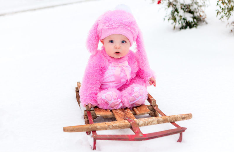 Portrait of cute baby girl sitting on sled during snow