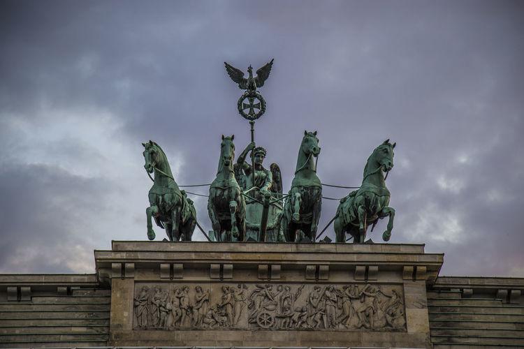 Low angle view of quadriga statue brandenburg gate against cloudy sky