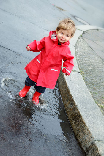 Portrait of happy girl playing in puddle