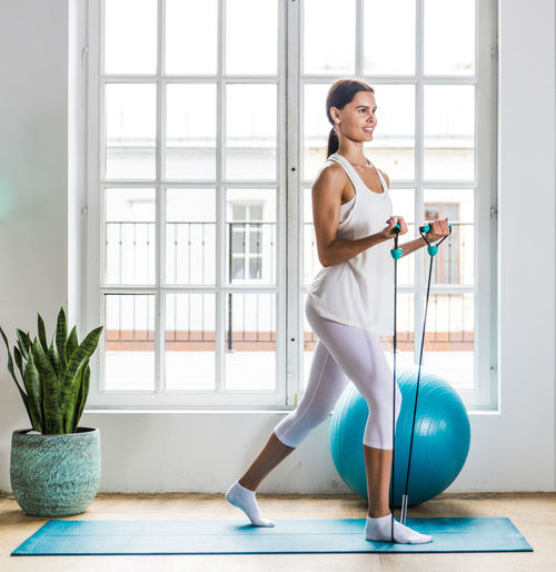 Young woman exercising with fitness ball at home