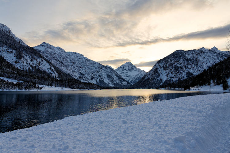 Scenic view of lake and snowcapped mountains against sky during sunset