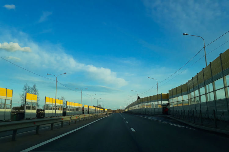 Vehicles on highway against sky in city