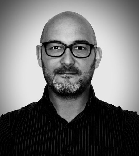 Portrait of man wearing eyeglasses against gray background