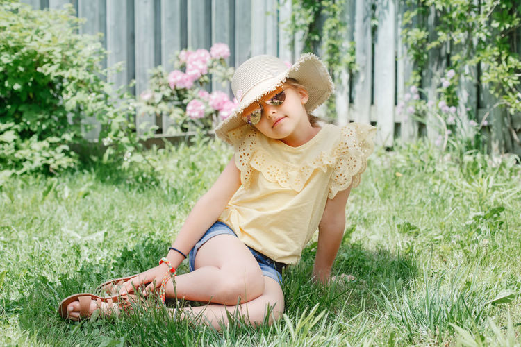 Portrait of girl sitting in grass at yard