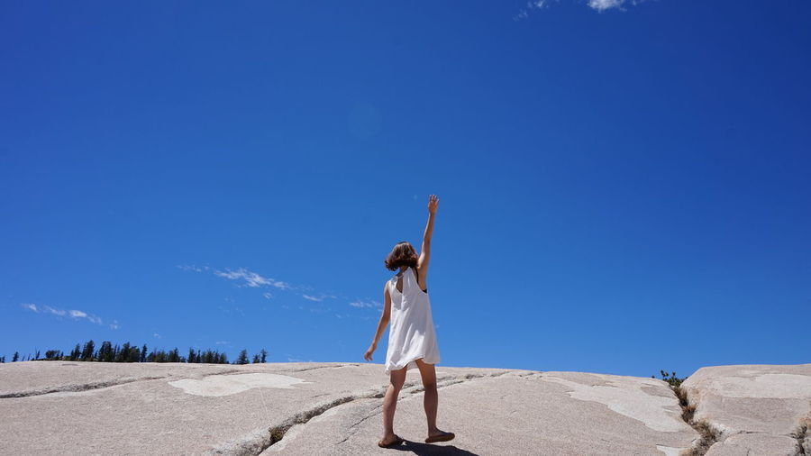 Rear view of woman with arms raised standing on cliff against blue sky