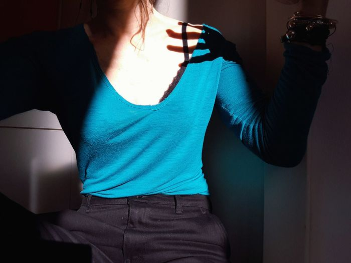 Midsection of woman sitting against wall at home