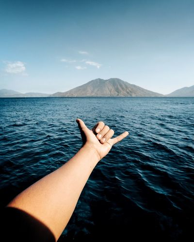 Cropped hand of woman gesturing over sea against sky