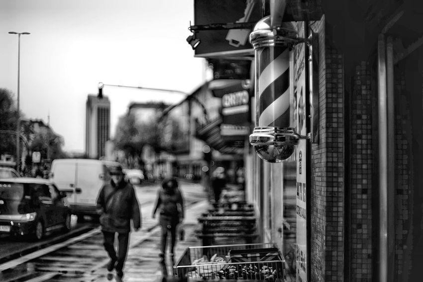 Rainy Days in BNW Blackandwhite Shopping Street Small Shop Wet Street Rainy Day Architecture Building Exterior Built Structure Day City Focus On Foreground Sky Street Nature Metal Men Building Outdoors Real People Hanging Walking Incidental People The Street Photographer - 2018 EyeEm Awards