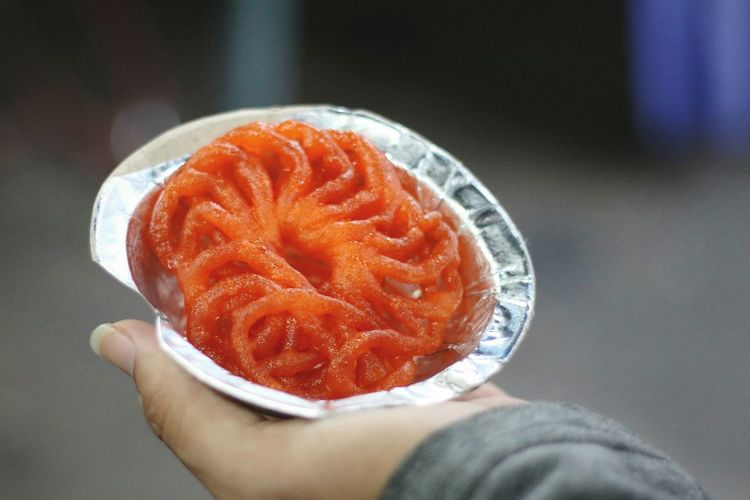 Close-up of person holding jalebi desert in plate