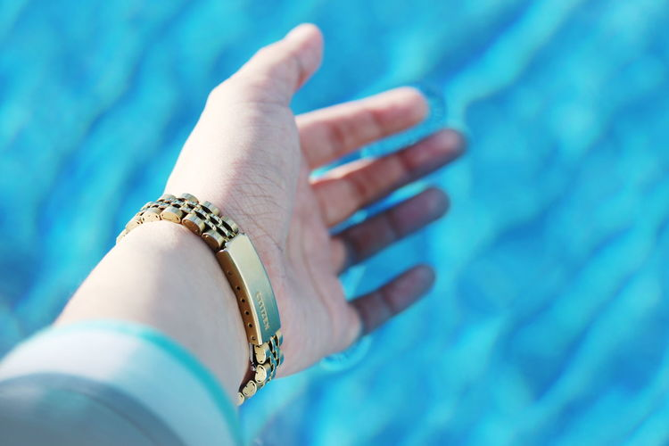 Close-up of woman hand on swimming pool