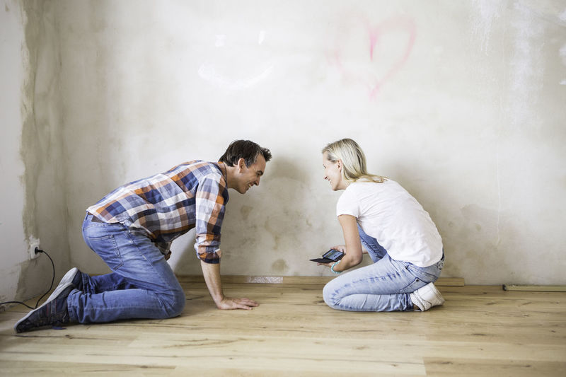 Young couple measuring a floor in a yoga studio Casual Clothing Day DIY Enjoyment Full Length Fun Jeans Leisure Activity Lifestyles Relationship Relaxation Rennovations Renovations Teamwork Yo