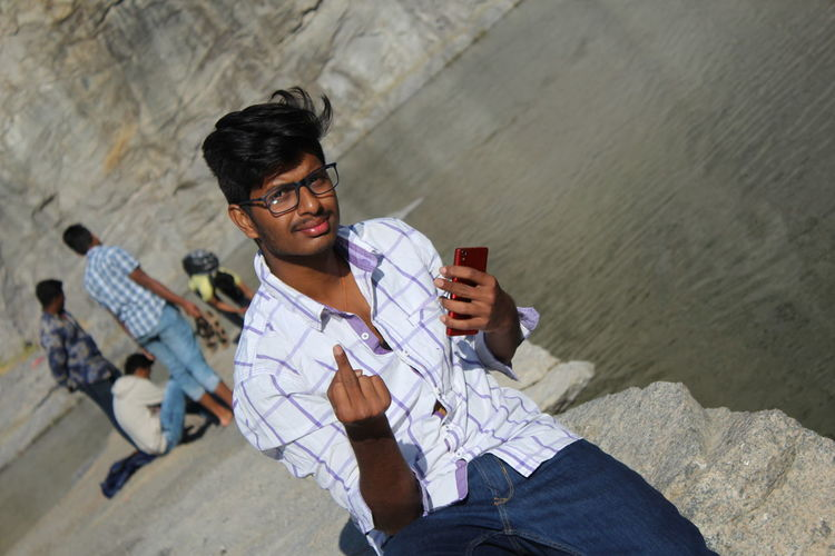 Portrait smiling young man with smart phone showing obscene gesture by lake