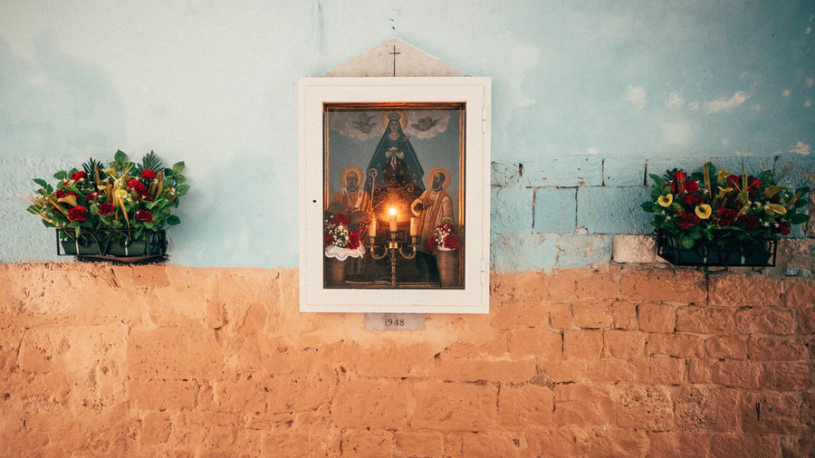 Virgin Mary Picture Frame And Flower Pots Attached To Wall