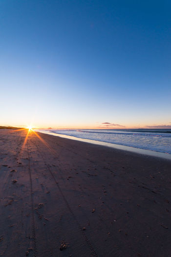 Papamoa beach at sunset with a sun star Beach Beauty In Nature Blue Clear Sky Horizon Over Water Landscape Nature New Zealand No People Outdoors Sand Scenics Sea Sun Sun Star Sunlight Sunset Tranquil Scene Travel Travel Destinations Water