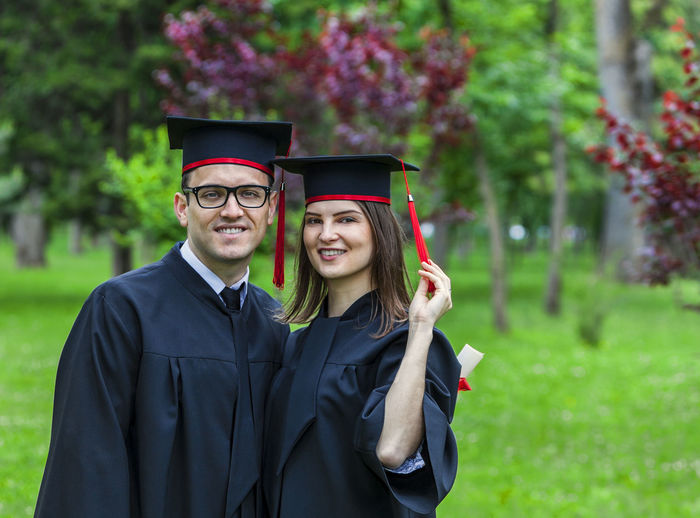Portrait of smiling students in graduation gown standing in park