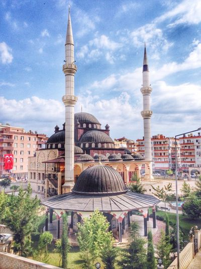 Blue Mosque In Center Of Residential Buildings Against Cloudy Sky