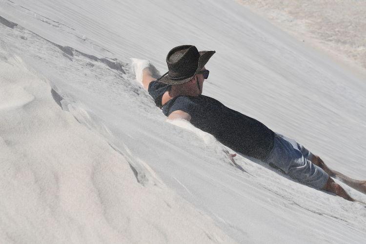 High Angle View Of Man Sliding On Sand Dune