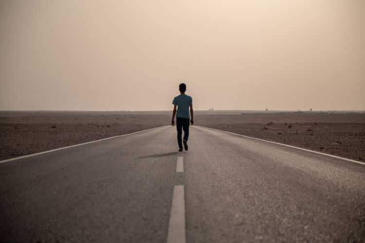 Rear view of man on road against sky