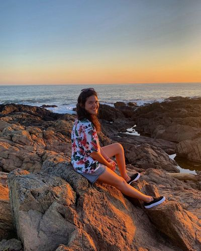 Portrait of smiling woman sitting on rock at beach against sky during sunset