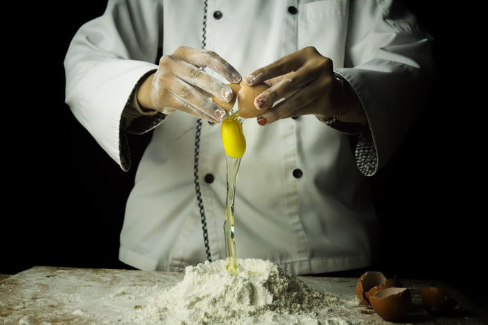 Pastry chef preparing dough in low light Cooking Low Light Baker Baking Preparati Chef Background Chef Hat Chef Uniforms Dark Background Day Dough Preparation Eggs First Eyeem Photo Flour Food Photography Food Preparation Human Hand Indoors  Kitchen Kitchen Background Kitchen Environme Making One Person Person