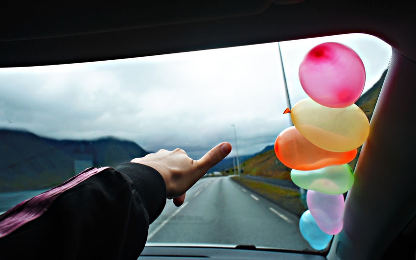 Rear view of person with balloons in car