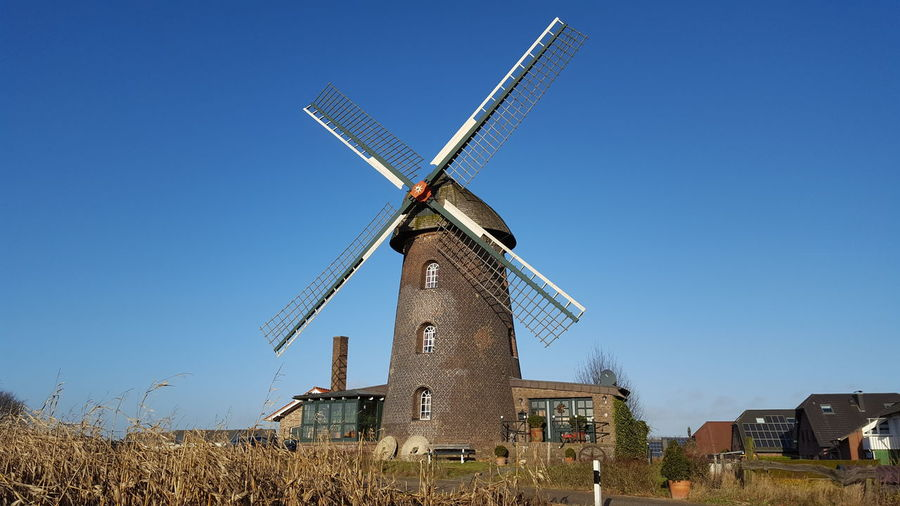 Traditional windmill on field against clear blue sky