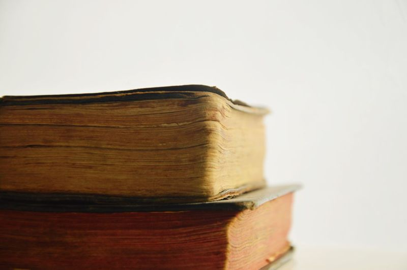 Close-up of stack of books against white background