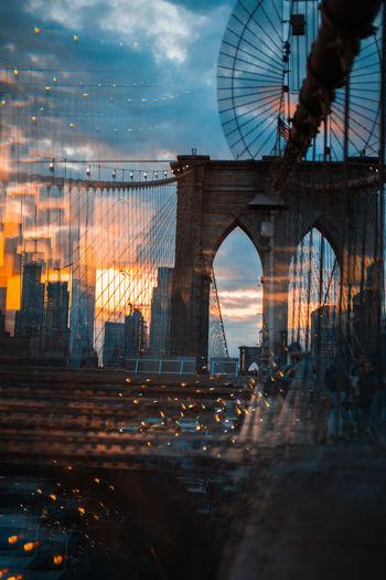 Bridge over illuminated city against sky during sunset