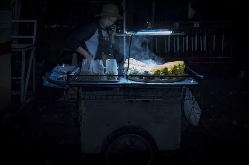 Woman talking on mobile phone while preparing food at market